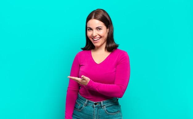 Jeune femme assez décontractée souriant joyeusement, se sentant heureux et montrant un concept dans l'espace de copie avec la paume de la main