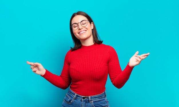Jeune femme assez décontractée souriante, se sentir insouciante, détendue et heureuse, danser et écouter de la musique, s'amuser lors d'une fête