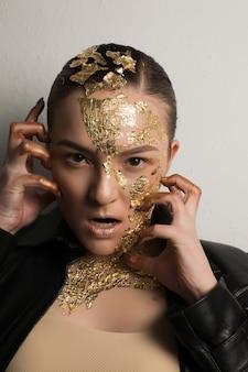 Jeune femme assez émotive avec une feuille d'or sur le visage, les cheveux et le cou