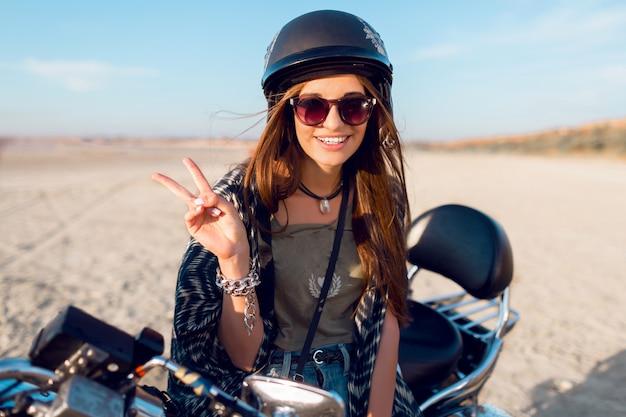 Jeune femme assez gaie assise sur une moto sur la plage et montrer des signes, portant un haut court élégant, des chemises, un corps apprivoisé mince et des poils longs. portrait de mode de vie en plein air.