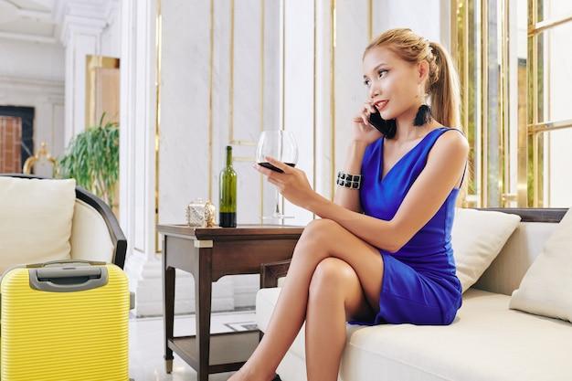 Jeune femme assez à la mode parlant au téléphone et buvant du vin en attendant un taxi dans le hall de l'hôtel