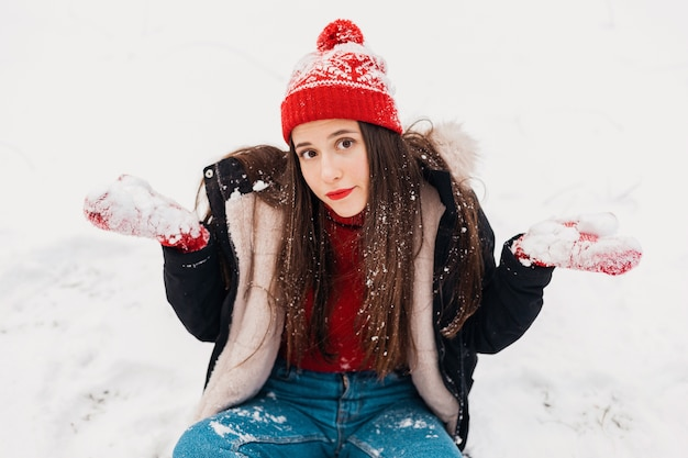 Jeune femme assez perplexe en mitaines rouges et bonnet tricoté portant un manteau d'hiver assis sur la neige dans le parc, des vêtements chauds