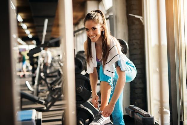 Jeune femme assez sportive attachant des lacets dans la salle de gym tout en écoutant de la musique.