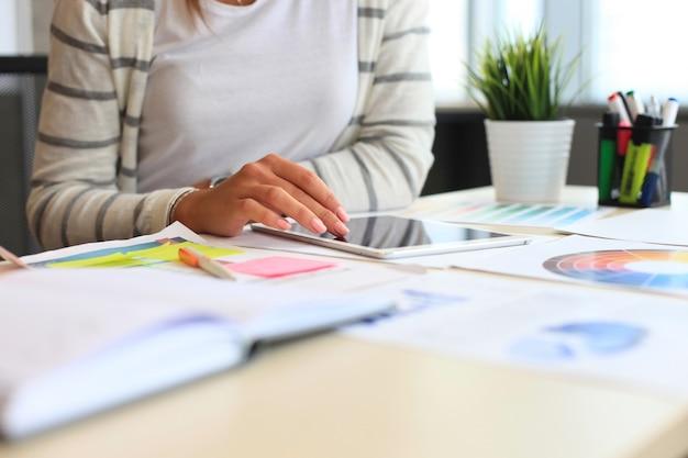 Jeune femme assise au bureau avec instruments, plan et ordinateur portable