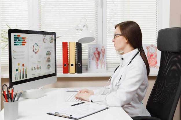 Jeune femme assise au bureau, travaillant sur un ordinateur moderne avec des documents médicaux dans un bureau léger à l'hôpital