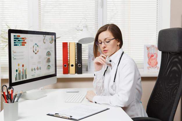 Jeune femme assise au bureau, travaillant sur ordinateur, remplissant des documents médicaux dans un bureau léger à l'hôpital