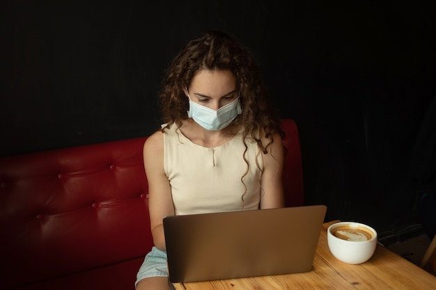 Jeune femme assise au café et travaillant sur un ordinateur portable avec un masque facial