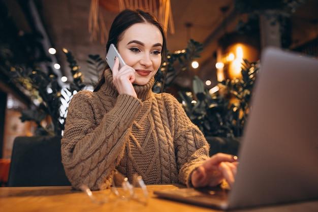 Jeune femme assise au café et travaillant sur un ordinateur portable