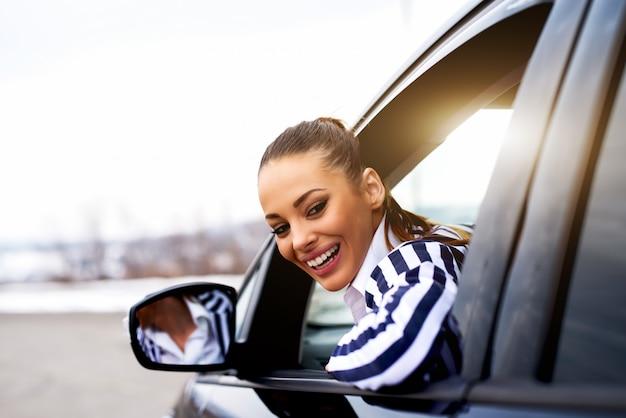 Jeune femme assise au siège du conducteur et regardant par la fenêtre.