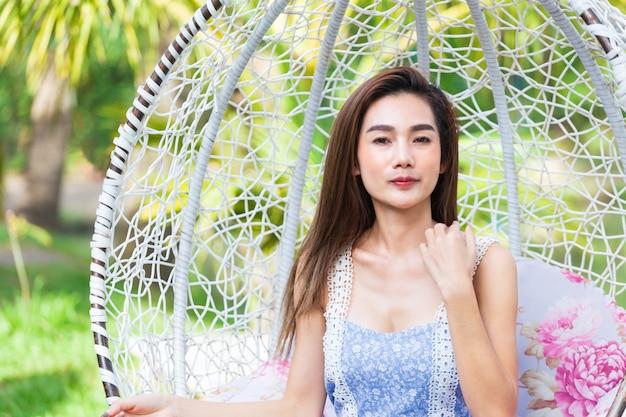Jeune femme assise en balançoire blanche