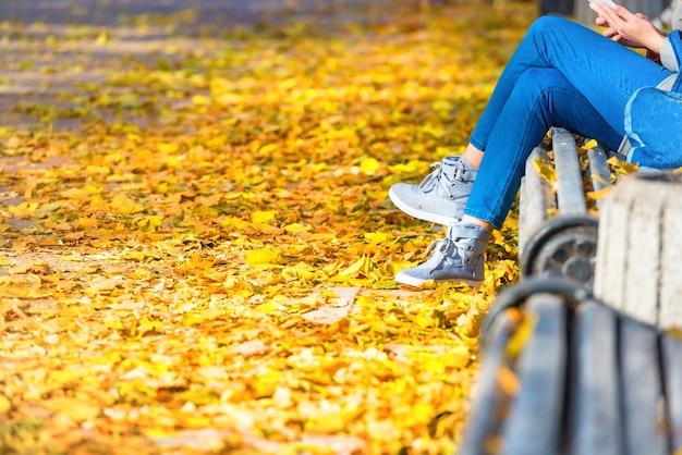 Jeune femme assise sur un banc dans un parc en automne avec des feuilles tombées jaunes