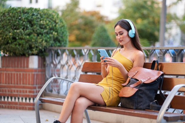 Jeune femme assise sur un banc dans la ville écoutant de la musique avec des écouteurs et regardant un message