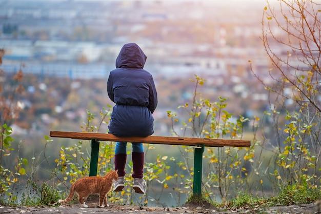 Jeune femme assise sur un banc en regardant la ville