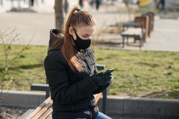 Jeune femme assise sur un banc de rue avec masque médical et vêtements noirs