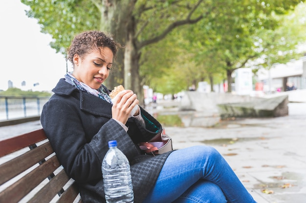 Jeune femme assise sur un banc en train de déjeuner à londres
