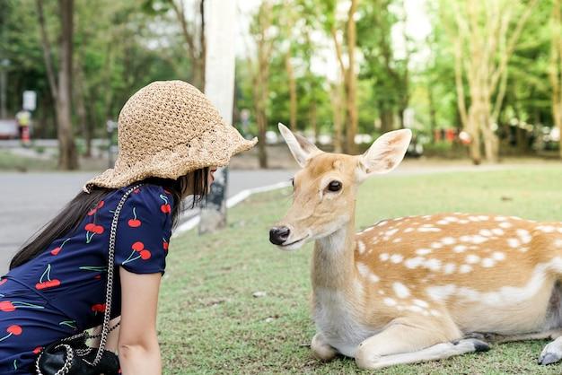 Jeune femme assise avec un beau cerf sauvage