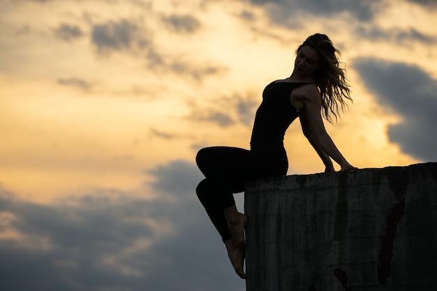 Jeune femme assise sur le bord avec le lever du soleil.