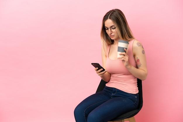 Jeune femme assise sur une chaise sur fond rose isolé tenant du café à emporter et un mobile