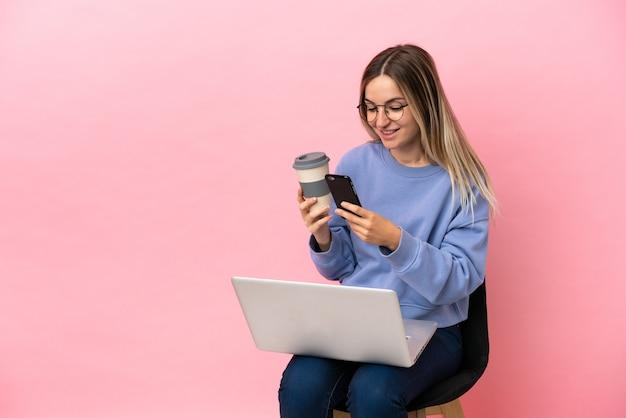 Jeune femme assise sur une chaise avec ordinateur portable sur fond rose isolé tenant du café à emporter et un mobile