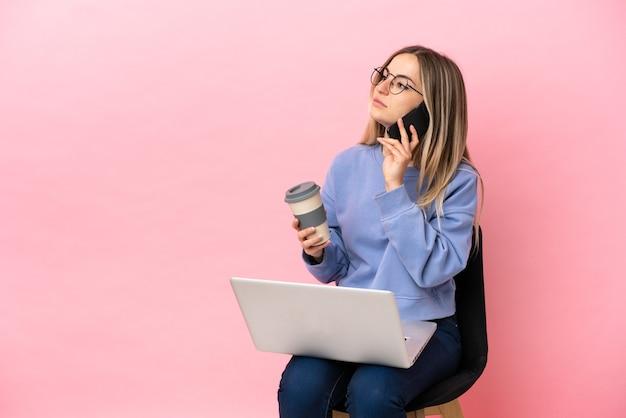 Jeune femme assise sur une chaise avec un ordinateur portable sur un mur rose isolé tenant du café à emporter et un mobile
