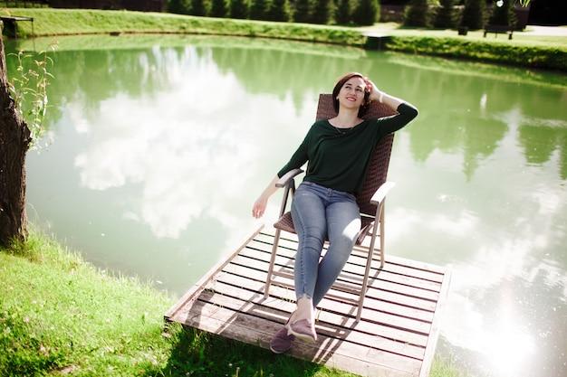 Jeune femme assise sur une chaise et se détendre sur la côte du lac dans le parc