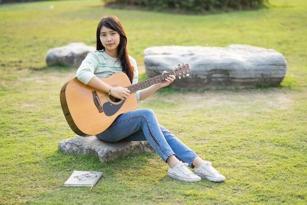 Jeune femme assise sur un champ et jouer de la guitare