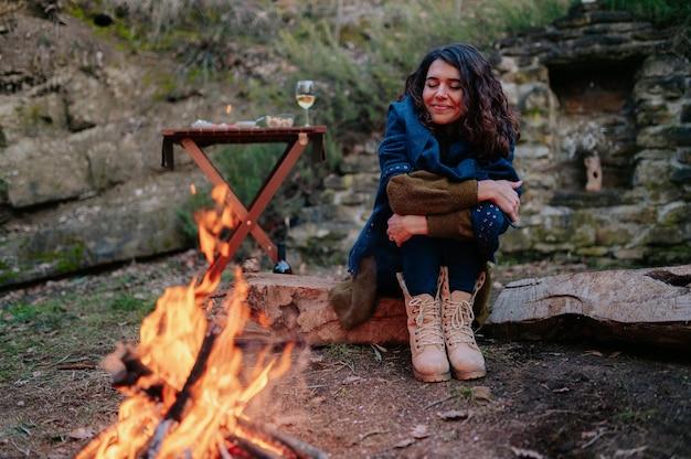 Jeune femme assise à côté d'un feu lors d'un pique-nique d'hiver.