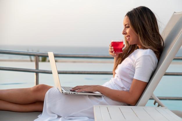Jeune femme assise à côté de la piscine avec un ordinateur portable sur ses genoux