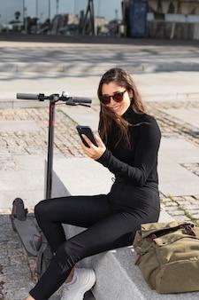 Jeune femme assise à côté de son scooter