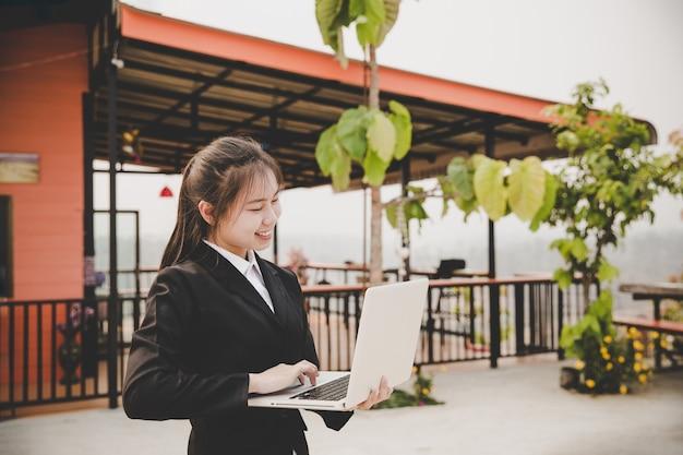 Jeune femme assise dans un café à une table en bois, boire du café. sur la table est un ordinateur portable.