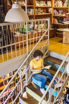 Jeune femme assise dans les escaliers avec livre