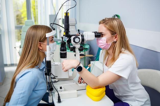 Jeune femme assise dans un fauteuil regardant une lampe à fente lors d'un examen médical dans les yeux