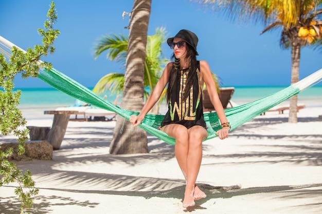 Jeune femme assise dans un hamac sur la plage