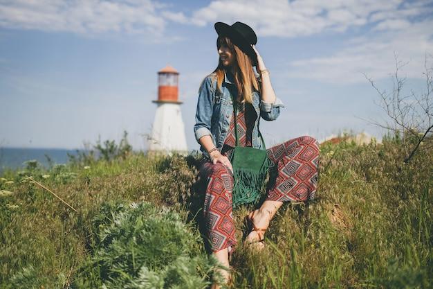 Jeune femme assise dans la nature, phare, tenue bohème, veste en jean, chapeau noir, souriant, heureux, été, accessoires élégants