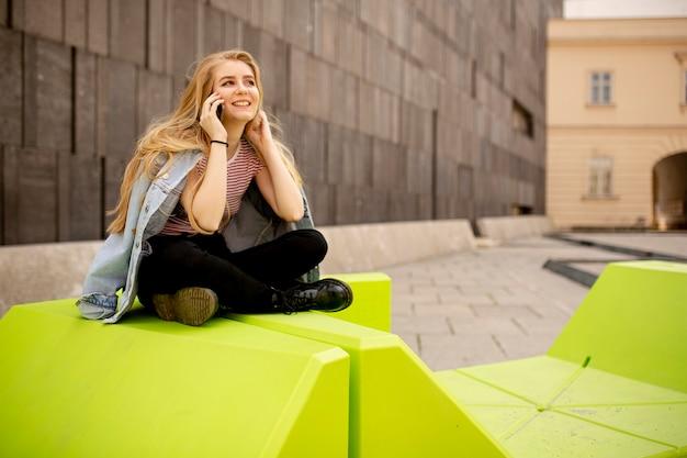 Jeune femme assise dans la ville et utiliser un téléphone mobile. concept urbain.