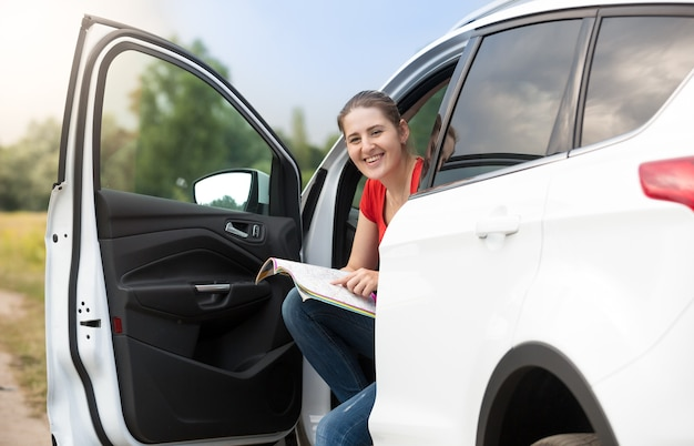 Jeune femme assise dans la voiture à la recherche de route sur la carte