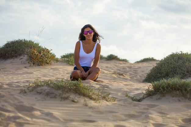 Jeune femme assise sur les dunes