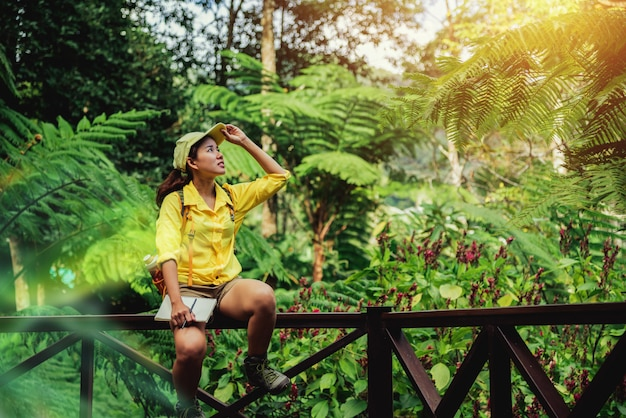 La jeune femme assise écrit, enregistre et étudie la nature de la forêt.