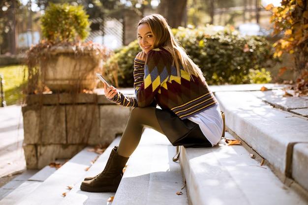 Jeune femme assise sur un escalier avec téléphone portable en automne parc