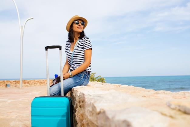 Jeune femme assise en face de la mer