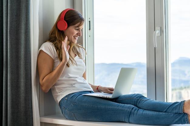 Jeune femme assise à la fenêtre pour effectuer un appel vidéo avec son ordinateur portable à la maison. concept de nouvelles technologies et réseaux sociaux à domicile.