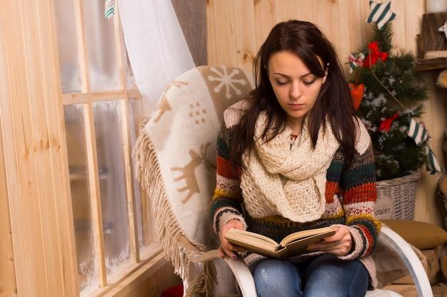 Jeune femme assise lisant dans une chaise en bois courbé à côté d'une fenêtre givrée à noël avec un tapis décoratif avec des rennes sur son épaule
