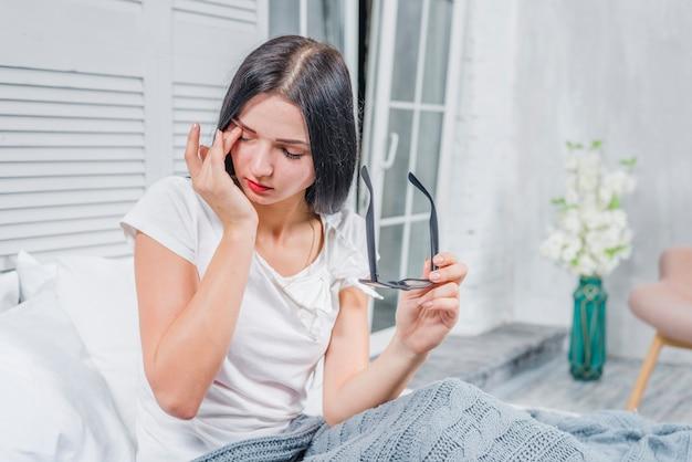 Jeune femme assise sur un lit se touchant les yeux dans la chambre