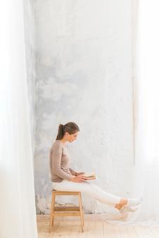 Jeune femme assise sur un livre de lecture de tabouret en bois