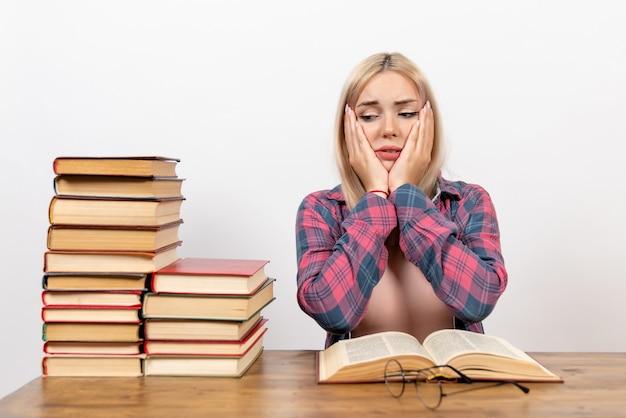 Jeune femme assise avec des livres et lisant sur blanc