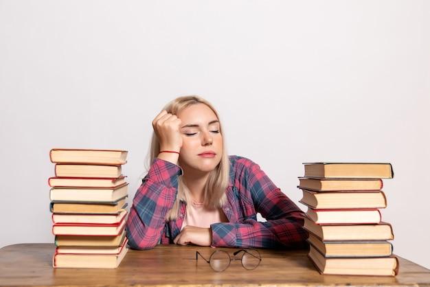 Jeune femme assise avec des livres se sentir fatigué sur blanc