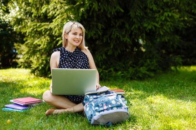 Jeune femme assise sur la pelouse dans une position de yoga avec un ordinateur portable