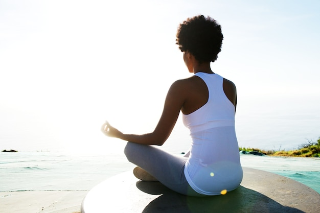 Jeune femme assise sur la plage dans la pose d'yoga