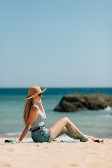 Jeune femme assise sur la plage de la mer