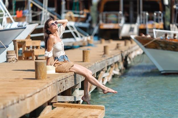 Jeune femme assise sur un pont de bois dans le port